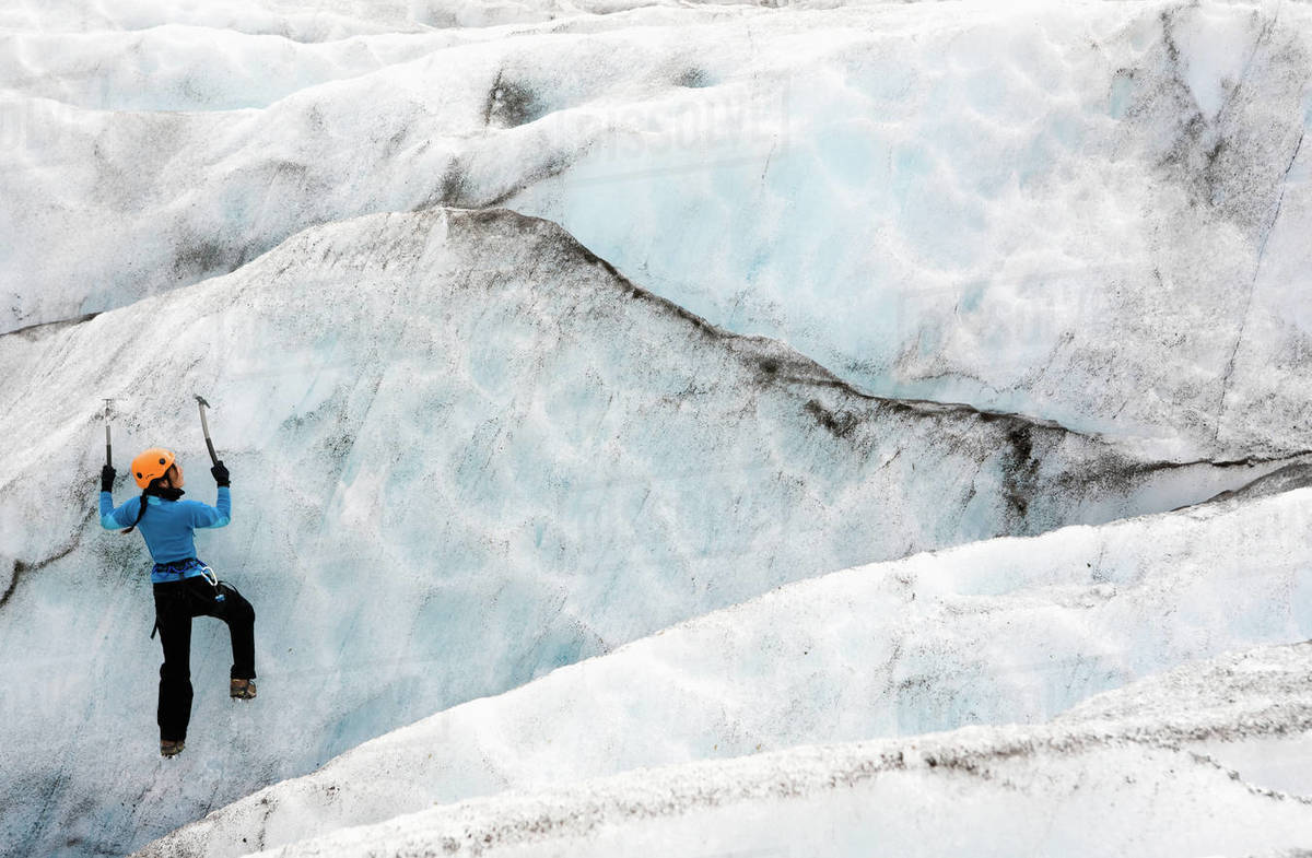 Woman climbing ice wall on Sólheimajökull glacier in Iceland Royalty-free stock photo