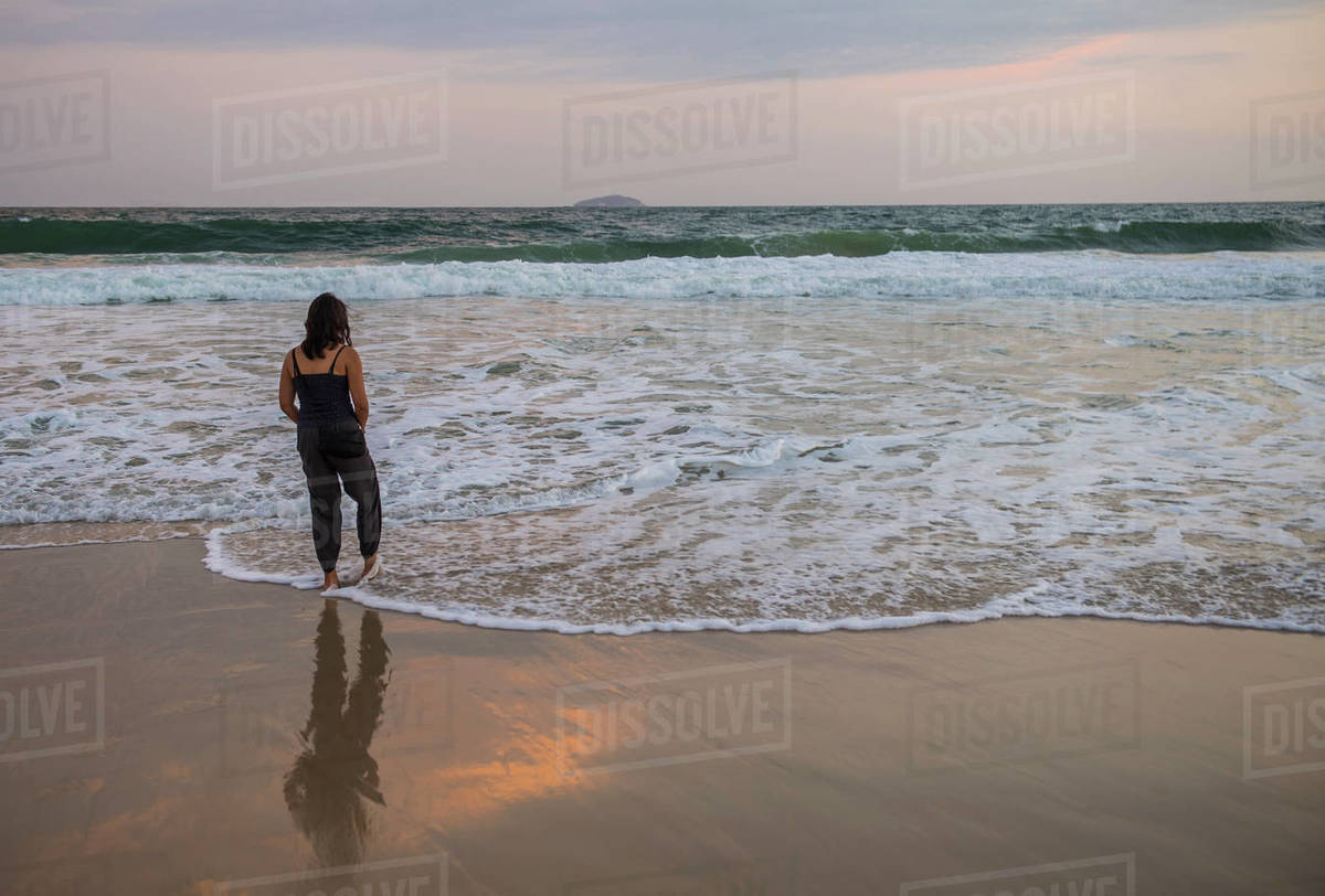 Woman tipping her toes in the Atlantic ocean in Rio de Janeiro Royalty-free stock photo