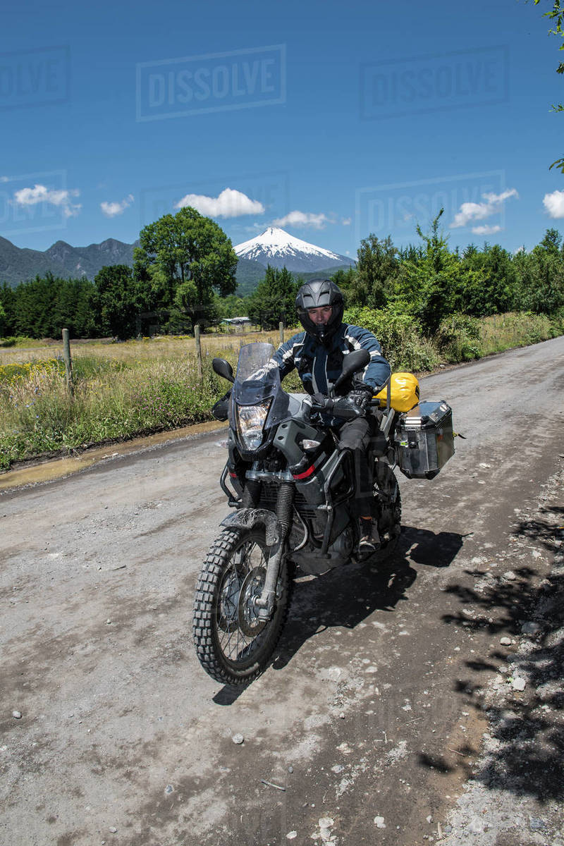 Motorbike rider passing the strato volcano Villarica, Chile Royalty-free stock photo