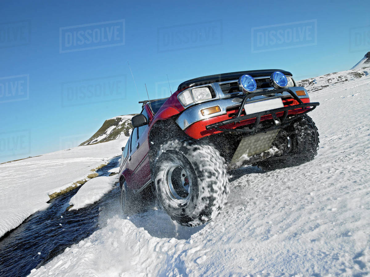 Red SUV crossing river in the winter on the Icelandic highlands Royalty-free stock photo