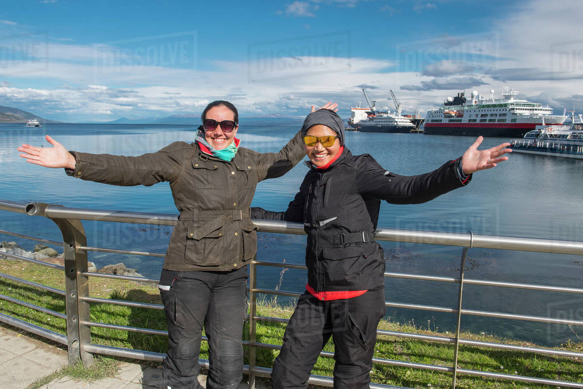 Two women in motorbike clothes posing at the harbour of Ushuaia Royalty-free stock photo