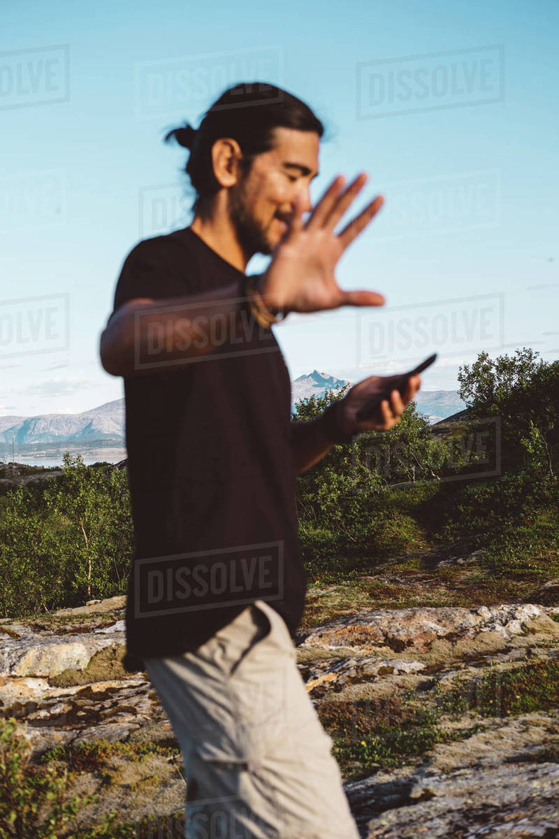 Man moving his arm towards the camera while he is looking at his phone Royalty-free stock photo