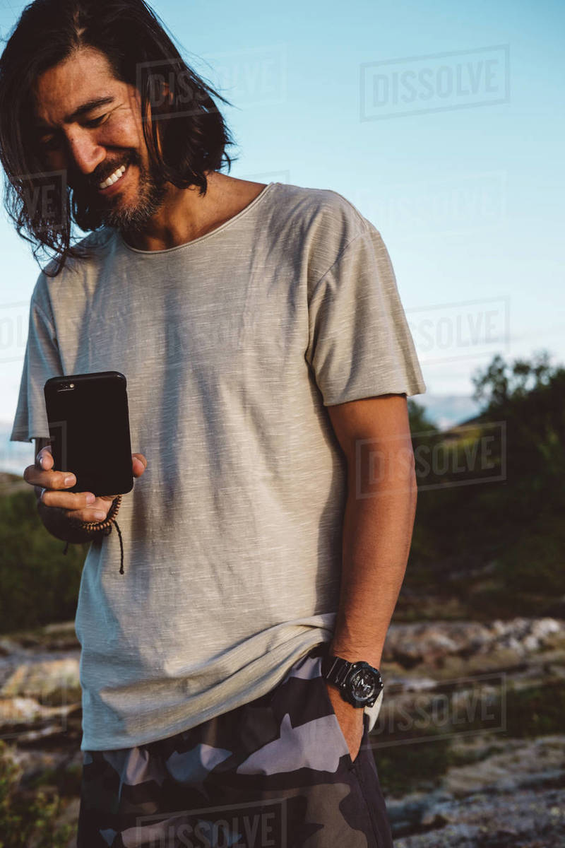 Man smiling taking a photo with his smartphone outdoors Royalty-free stock photo