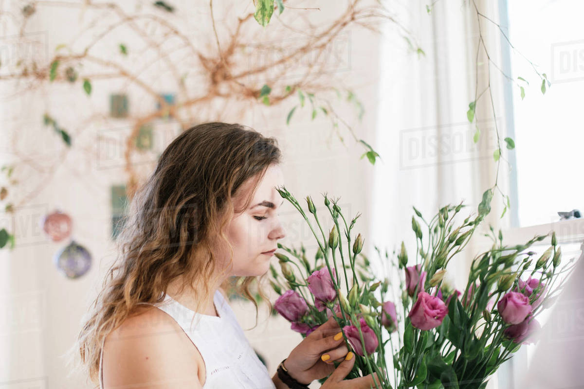 Boho teenager smelling fresh flowers isolate at home Royalty-free stock photo