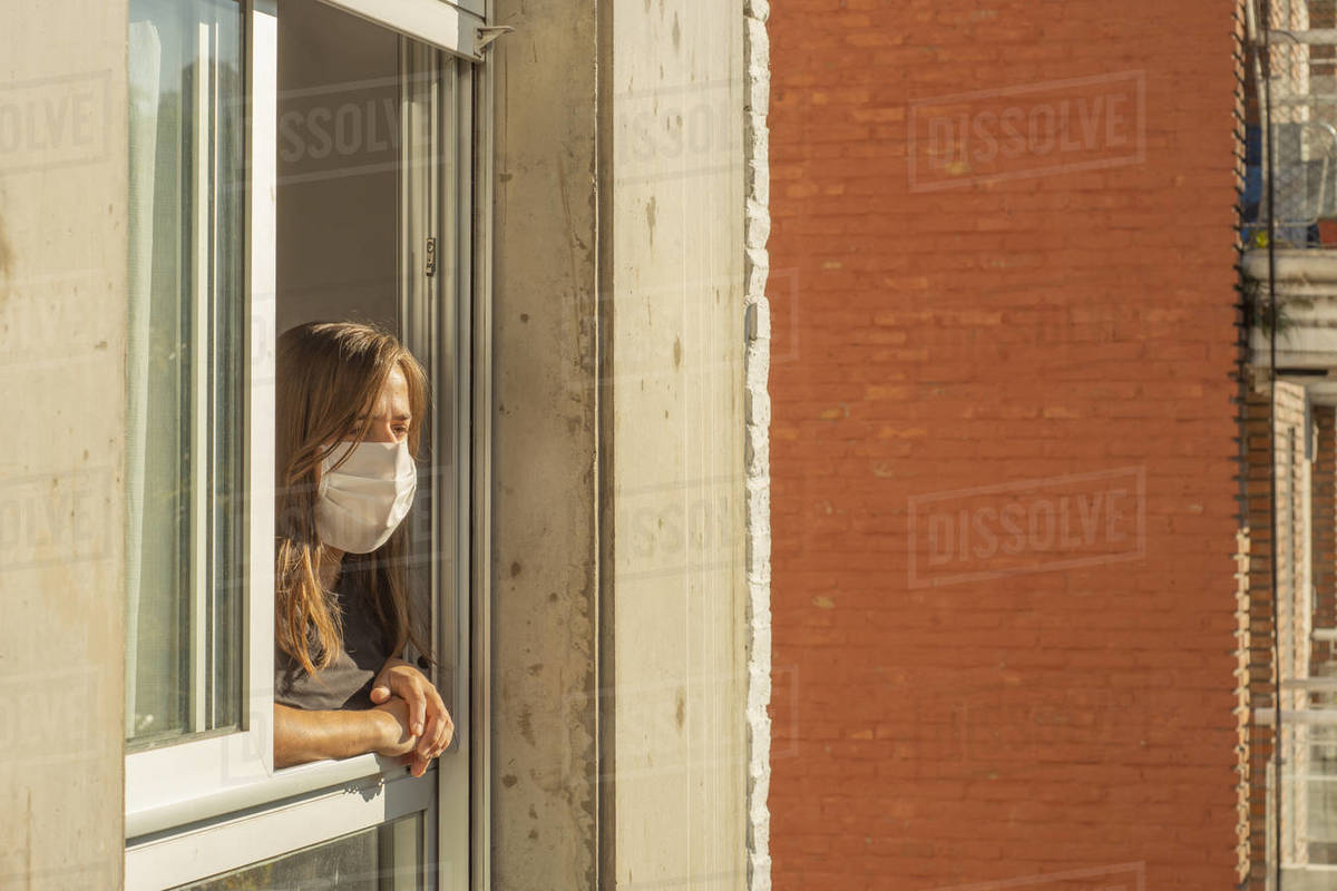 Woman in the windows during quarantine using a mask Royalty-free stock photo