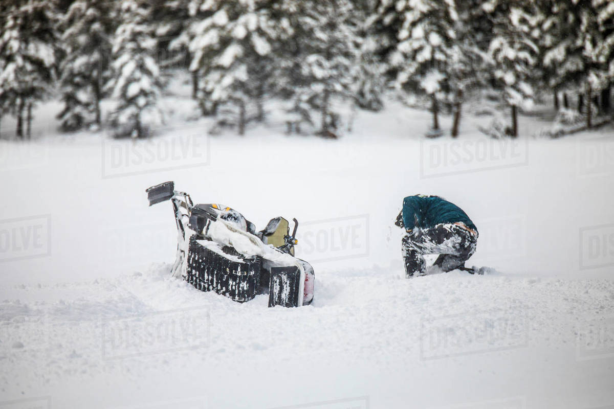 Snowmobiler crashes his sled during failed high-speed stunt Royalty-free stock photo