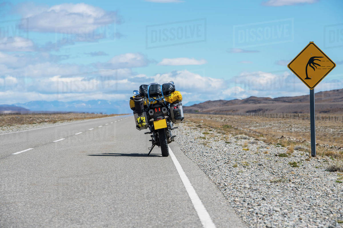 Adventure motorbike parked next to wind warning sign in Argentina Royalty-free stock photo