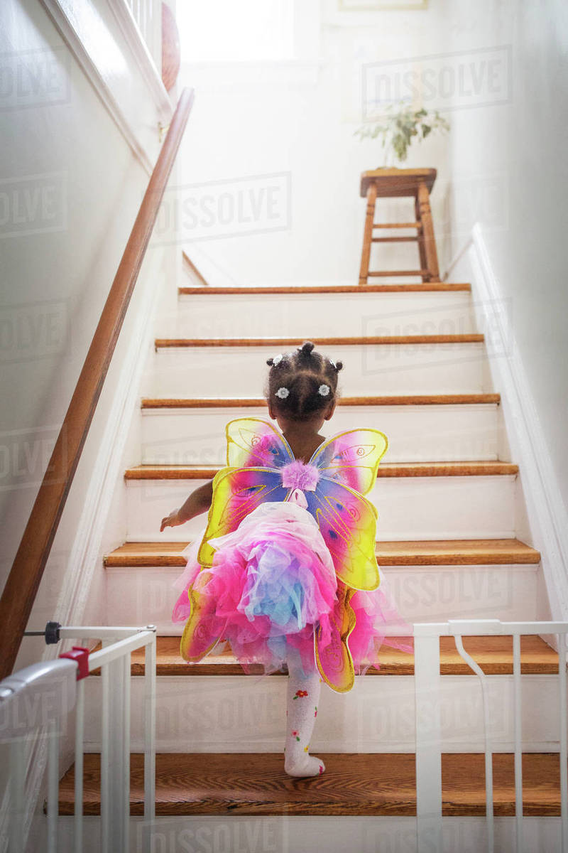Rear view of girl dressed up in fairy costume moving up steps at home Royalty-free stock photo