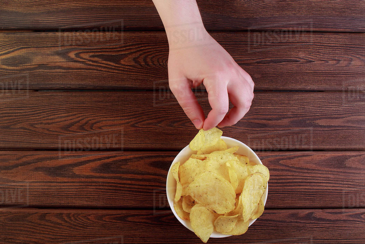 Hand holding Potato chips on dish isolated on wooden background Royalty-free stock photo