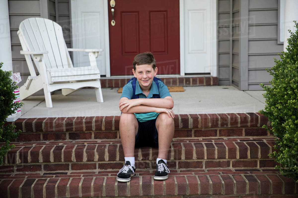 Smiling Tween Boy With Braces Sits on Brick Front Steps Royalty-free stock photo