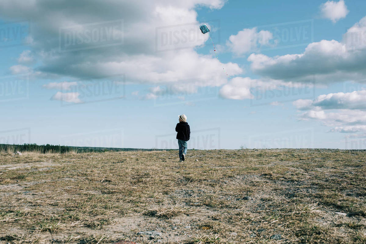 Young boy flying a kite on a hill on a beautiful sunny day Royalty-free stock photo