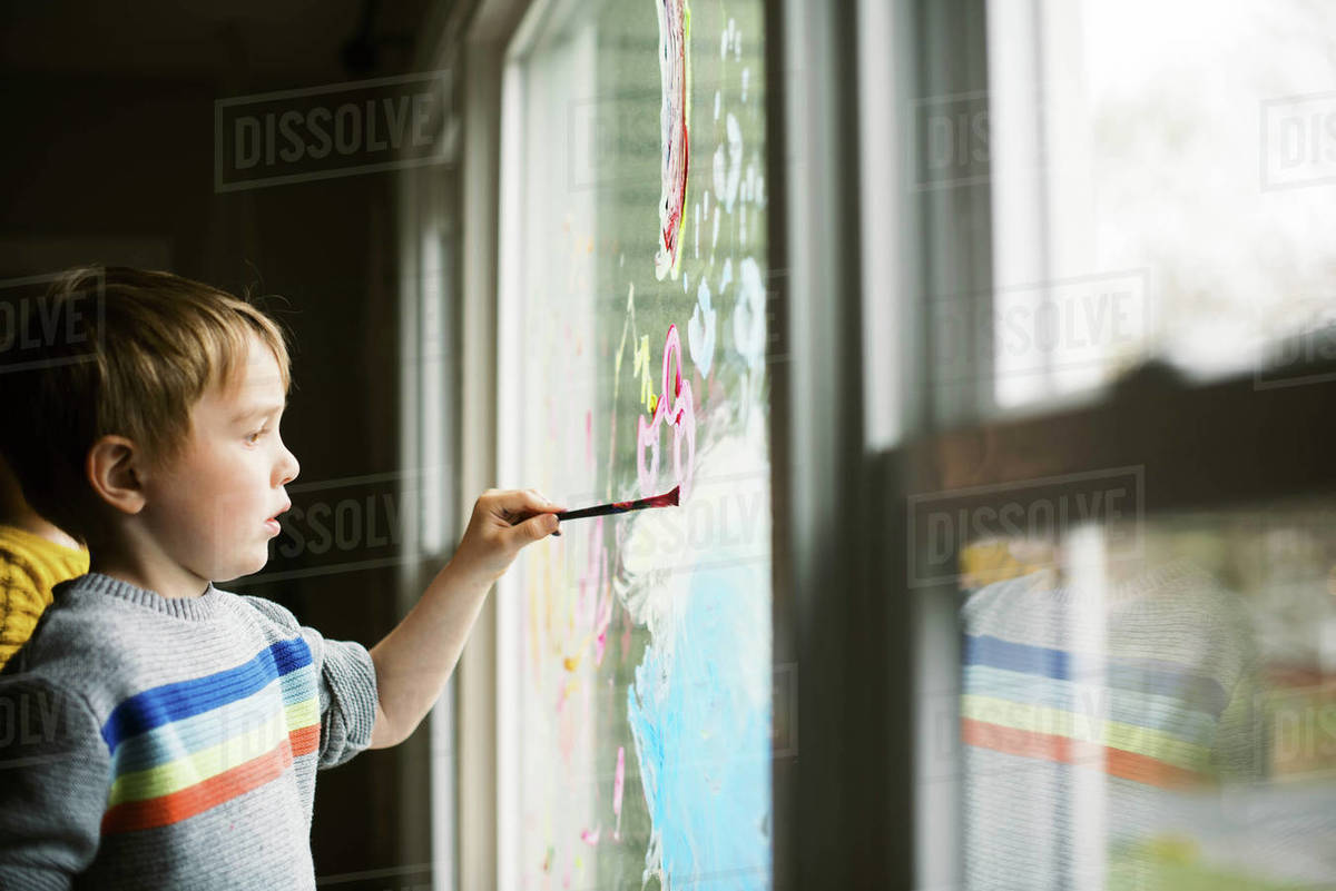 Two children coloring the kitchen window with finger parts together. Royalty-free stock photo