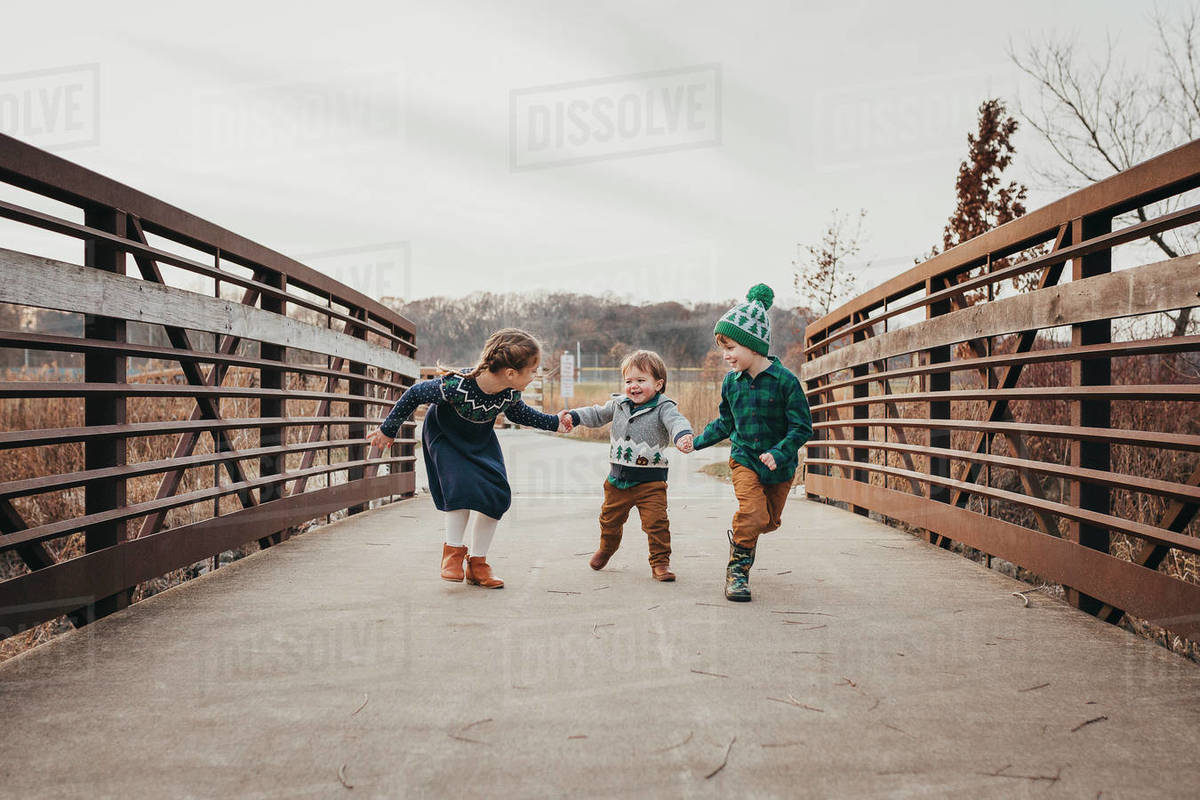 Three siblings laughing holding hands running on bridge Royalty-free stock photo