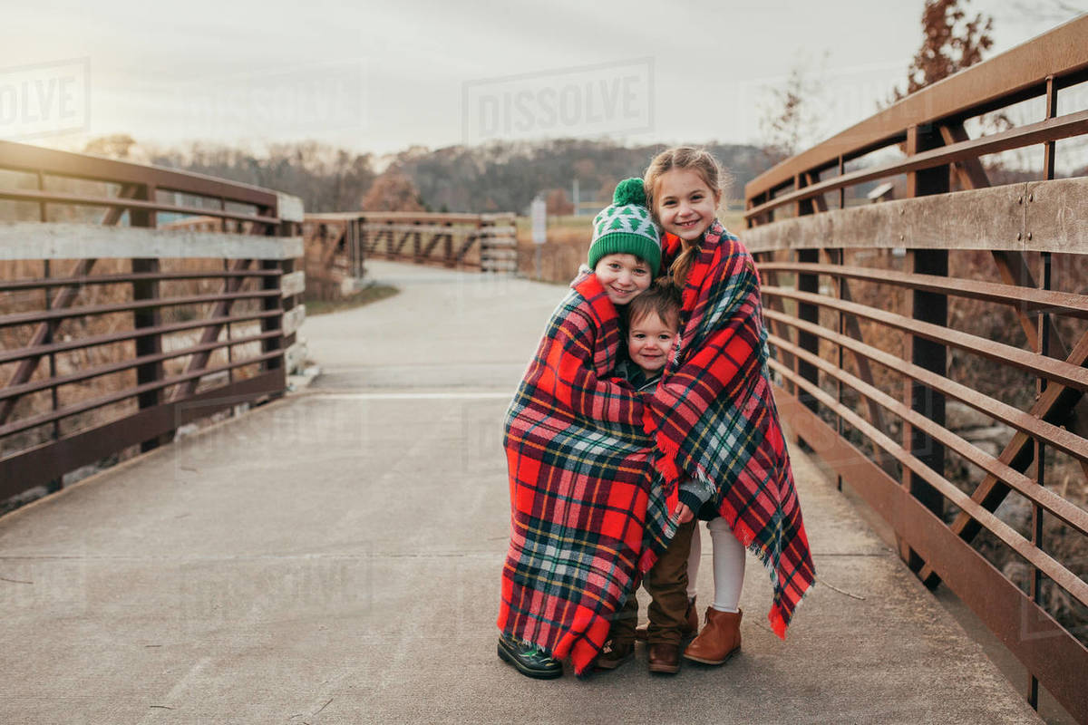 Siblings wrapped in Christmas plaid blanket on bridge at sunset Royalty-free stock photo