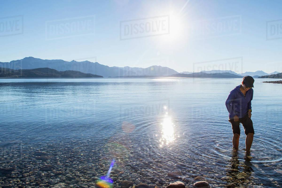 Woman trying the water at Nahuel Huapi Lake in Patagonia Royalty-free stock photo