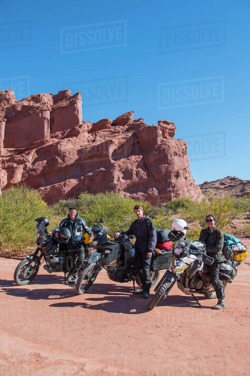 Group of friends standing beside touring motorbikes in desert Royalty-free stock photo