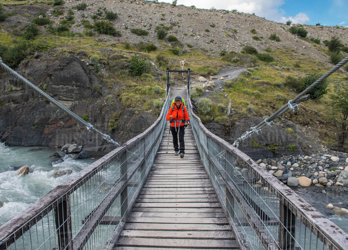 Female hiker crossing bridge at Torres del Paine national park Royalty-free stock photo