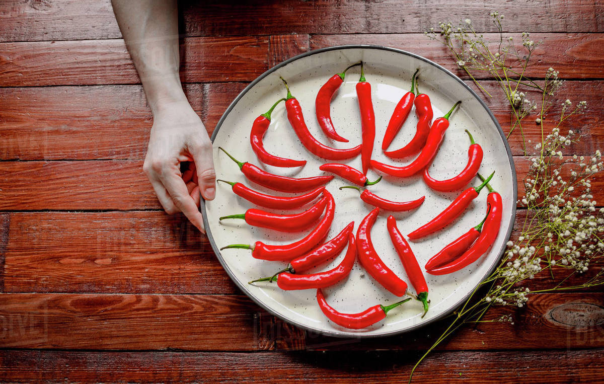 Red hot chilli peppers in a white tray on wooden background. Spicy. Royalty-free stock photo