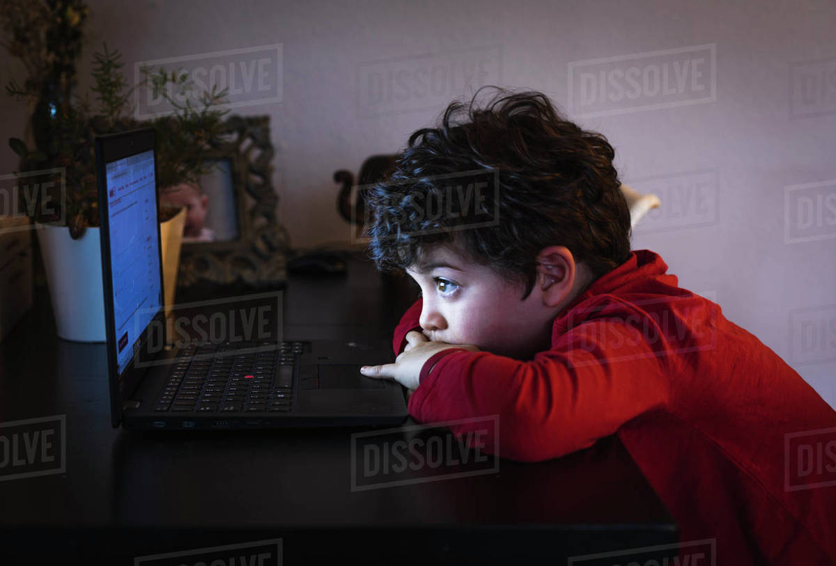 A child looks at his computer during confinement due to Covid-19. Royalty-free stock photo