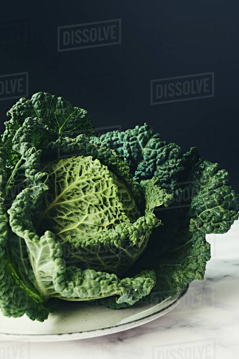 Ripe leafy green savoy cabbage head on marble and dark background Royalty-free stock photo