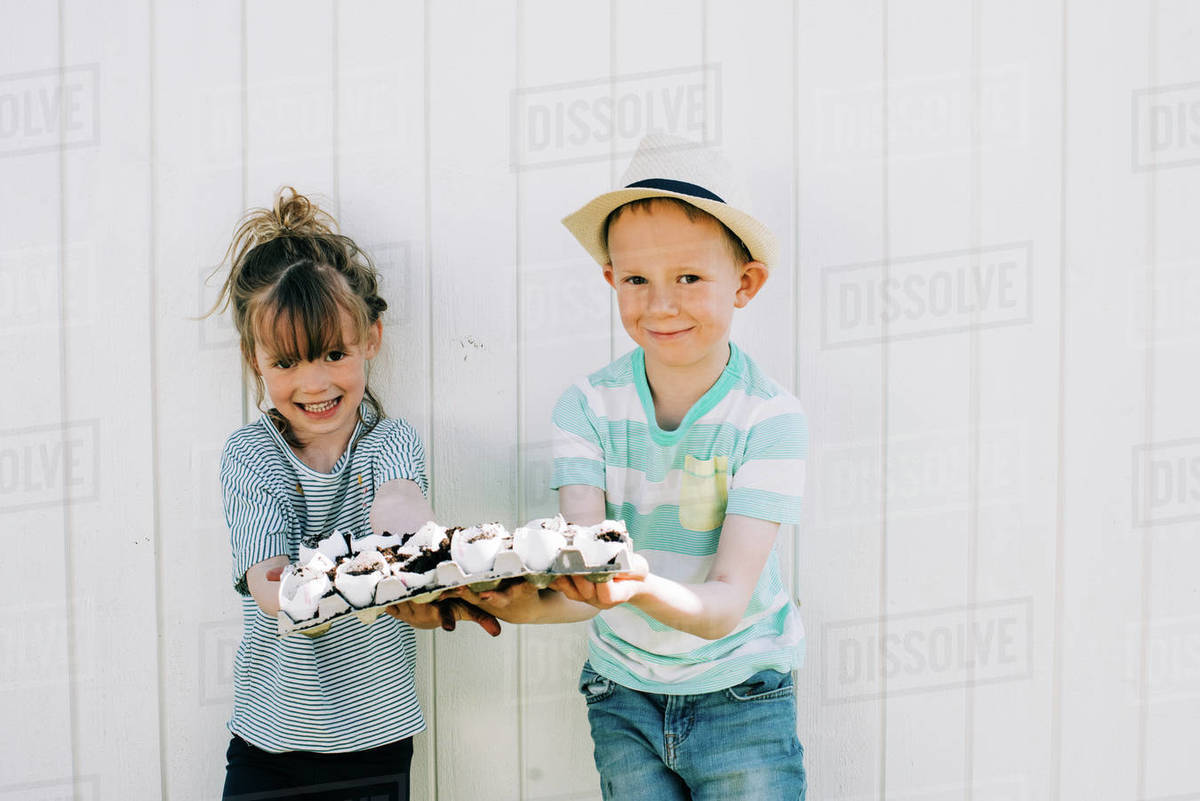 Siblings holding up their egg shells that they planted seeds into Royalty-free stock photo