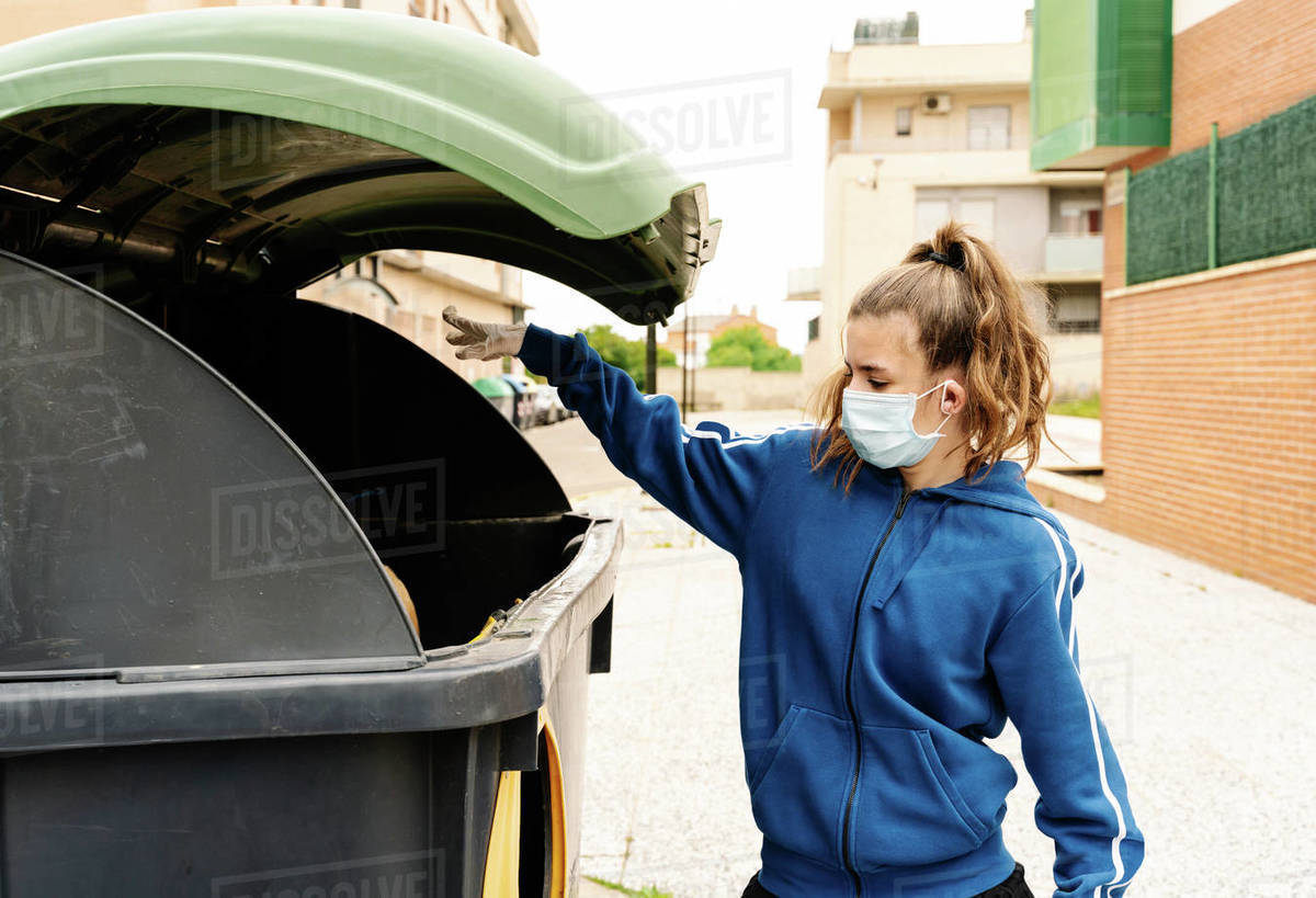 Girl throwing the a yellow trash bag into a green recycling container open in the street. The teenager is wearing face mask and gloves to protect herself from infections, virus, bacterias. Ho Royalty-free stock photo