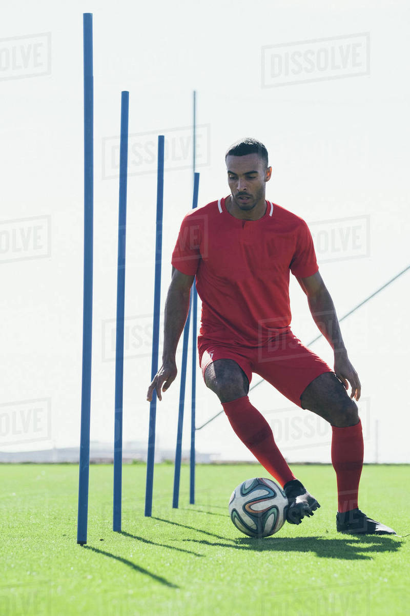 African American male soccer player practicing on grass pitch Royalty-free stock photo