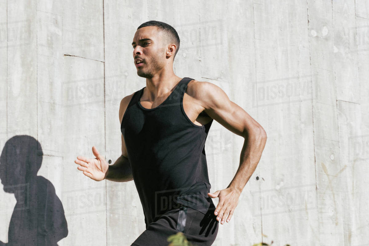 Upper part African American male athlete running against concrete wall Royalty-free stock photo