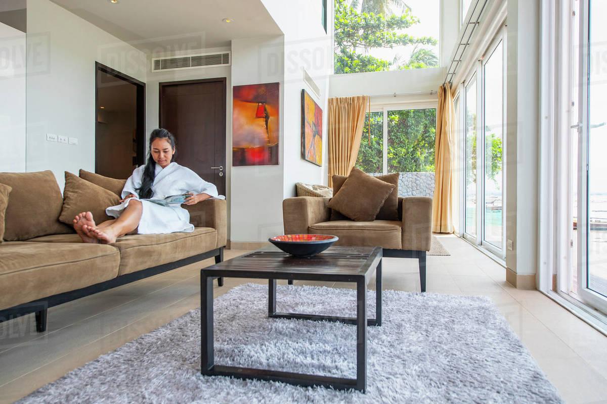 Beautiful woman reading at living room of luxury villa in Phuket Royalty-free stock photo