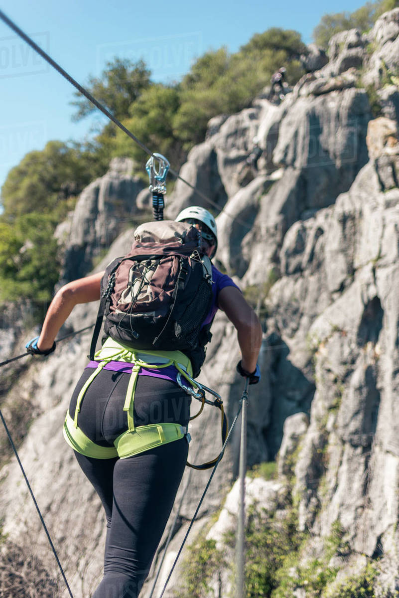 Concept: adventure. Woman with helmet, harness and backpack. Walking over the abyss over a monkey bridge. doing via ferrata in the mountains. Royalty-free stock photo