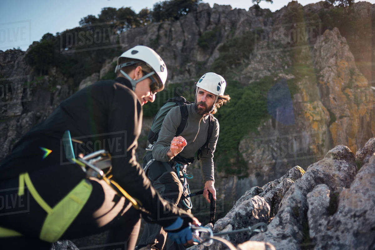 Concept: adventure. Man and woman with helmet, harness. Explaining climbing techniques. Solar luminous flare.Via ferrata in the mountains. Royalty-free stock photo