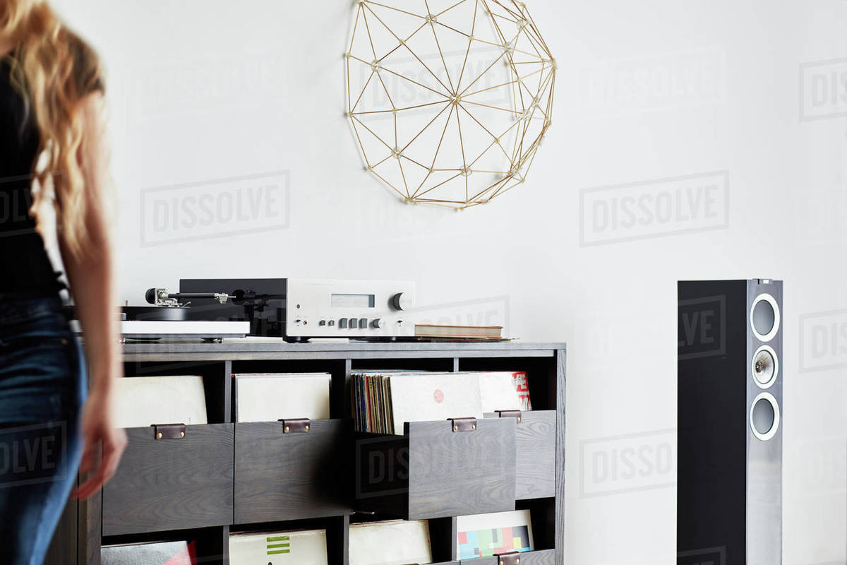 Woman next to stereo console with vinyl storage Royalty-free stock photo