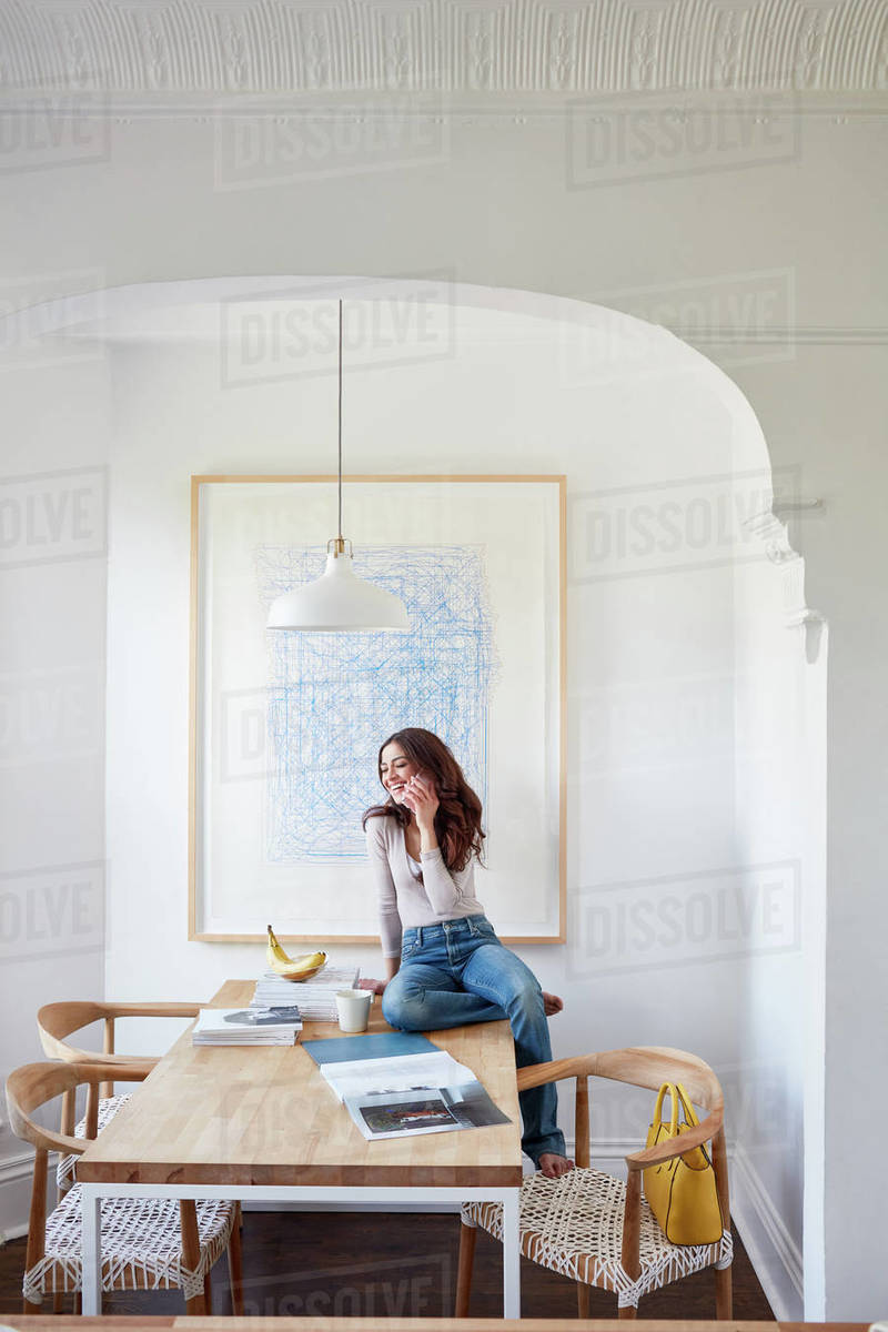 Woman on cell phone on kitchen table in nook Royalty-free stock photo