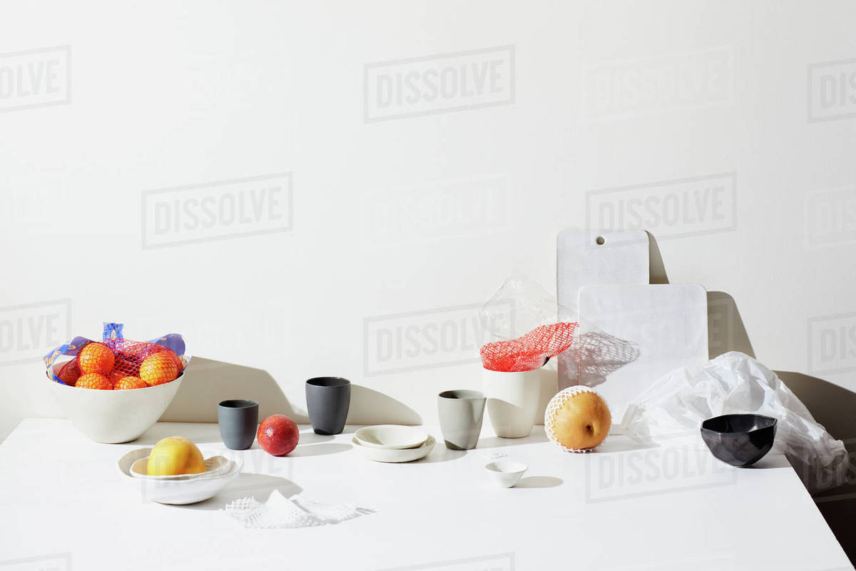 Still life with fruits, pottery cups and surfaces Royalty-free stock photo