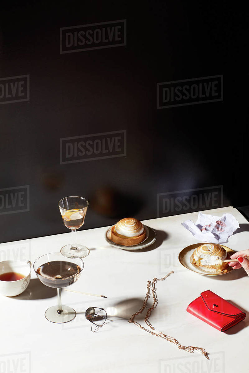 Still life of clutch purse, necklace, after dinner drinks and deserts Royalty-free stock photo