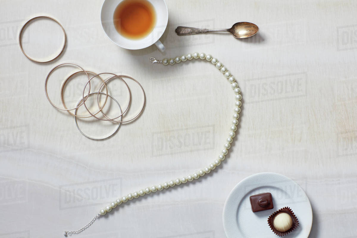Still life with tea cup, jewelry, necklace, chocolates Royalty-free stock photo