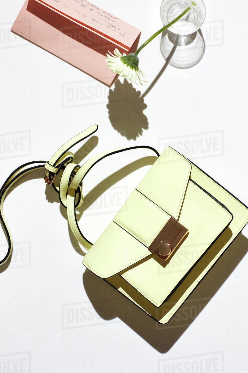 Fashion purse with flower, letter on white surface Royalty-free stock photo