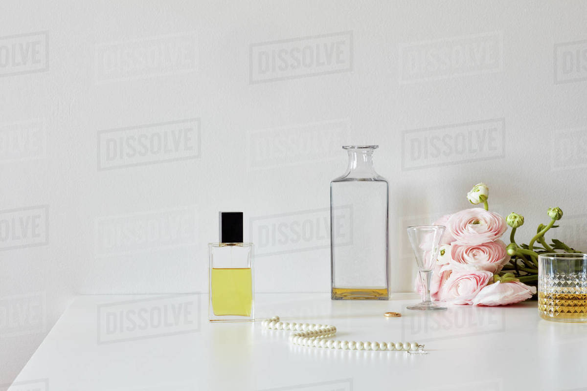Still life with perfumes, whiskey, necklace, roses Royalty-free stock photo