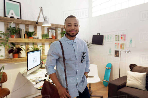 Portrait of smiling male illustrator carrying bag while standing in creative office Royalty-free stock photo