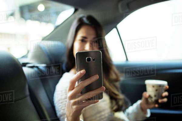Young woman photographing through smart phone in taxi Royalty-free stock photo
