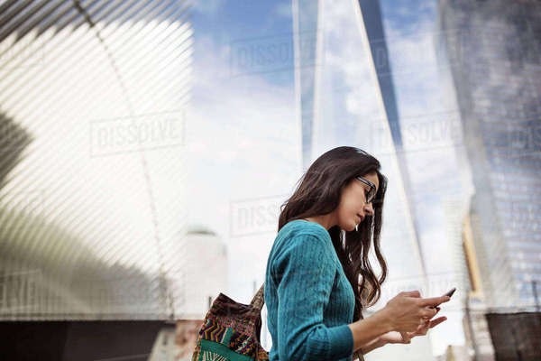 Side view of woman using smart phone outside One World Trade Center Royalty-free stock photo