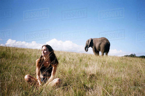 Thoughtful woman sitting on landscape with elephant in background Royalty-free stock photo