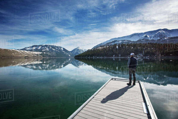 Rear view of man looking at Wallowa Mountains while standing on pier Royalty-free stock photo