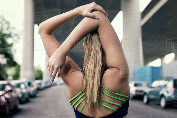 Rear view of Female Athlete doing stretching exercise under bridge in city Royalty-free stock photo