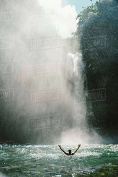 Rear view of man with arms outstretched in river by majestic waterfall Royalty-free stock photo