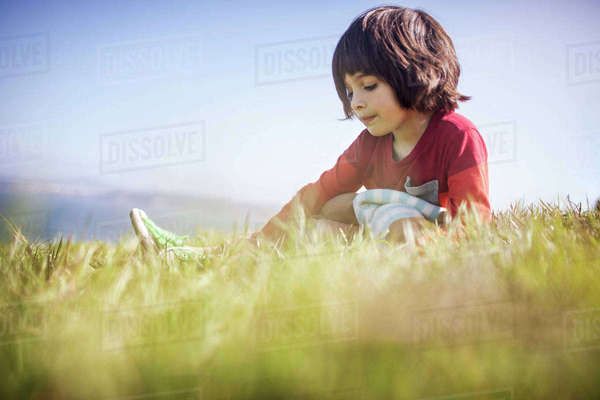 Cute boy sitting on grassy field Royalty-free stock photo