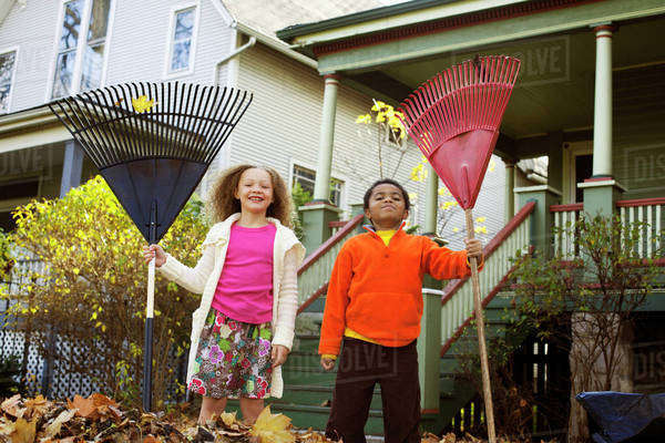 Two Friends (8-9) Playing with Rakes in Autumn Leaves Royalty-free stock photo