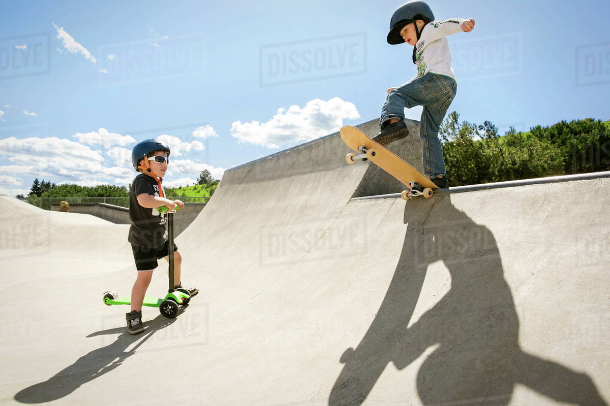 Skate Board Ramp >> Boy Looking At Friend Performing Stunt On Skateboard Ramp Stock