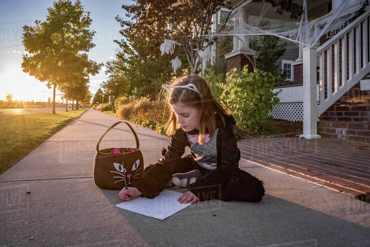 A young girl in a cat costume writes a note to the toothless fairy Royalty-free stock photo