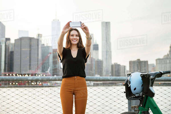 Woman taking selfie while standing by bicycle against river in city Royalty-free stock photo